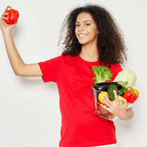 Young woman with clear skin holding fresh vegetables